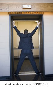 Rear view of a businessman stopping an elevator