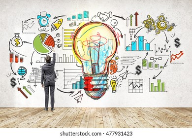 Rear view of businessman in suit drawing colorful startup sketch. Large light bulb icon in center. Concept of successful startupper