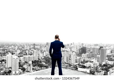 Rear view of a businessman talking on the phone on top of the building