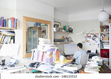 Rear view of businessman using computer in creative office space