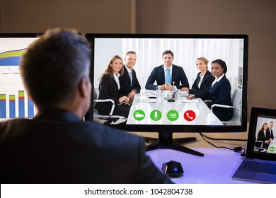 Rear View Of A Businessman Video Conferencing With Happy Colleagues On Computer At Workplace