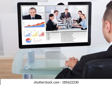 Rear view of businessman video conferencing with team on computer in office