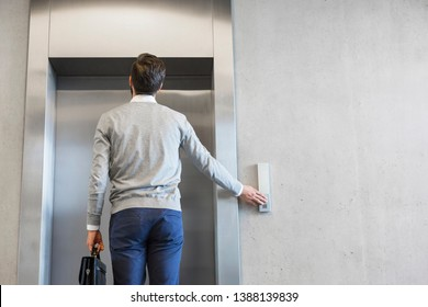Rear view of businessman waiting for elevator at office
