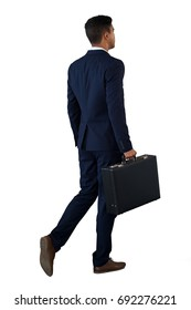 Rear view of businessman walking with briefcase against white background