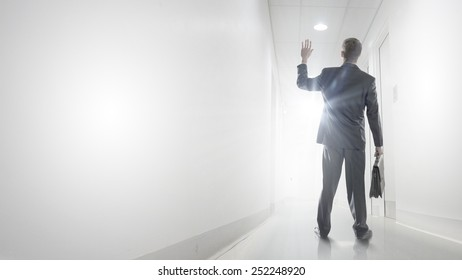 Rear view of businessman walking in office corridor