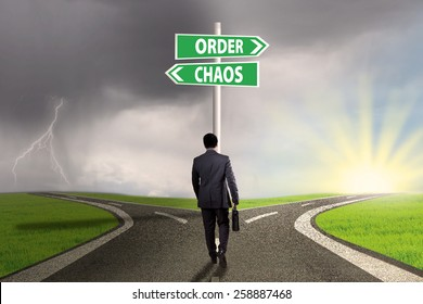 Rear view of businessman walking on the road with two choices to the right way or chaos