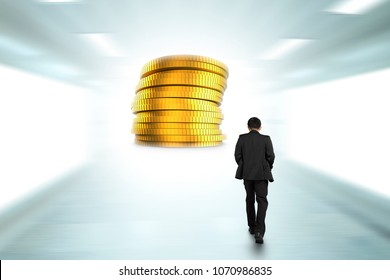 Rear view of businessman walking toward stack of golden coins.