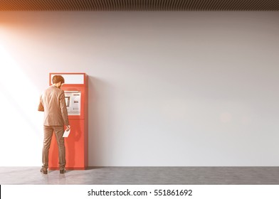 Rear view of a businessman withdrawing cash from a red ATM machine. Concept of financial operations. Mock up. Toned image