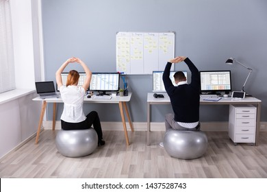 Rear View Of Businesspeople Sitting On Fitness Ball With Arm Raised At Workplace