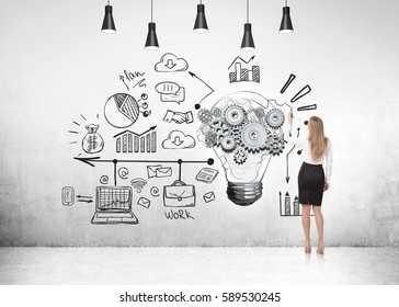 Rear view of a businesswoman in a black skirt looking at a light bulb with gears and a business timeline sketch on a concrete wall.
