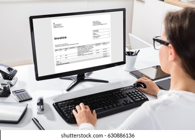 Rear View Of A Businesswoman Calculating Invoice On Computer At Workplace