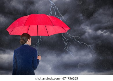 Rear view of businesswoman carrying red umbrella against stormy sky