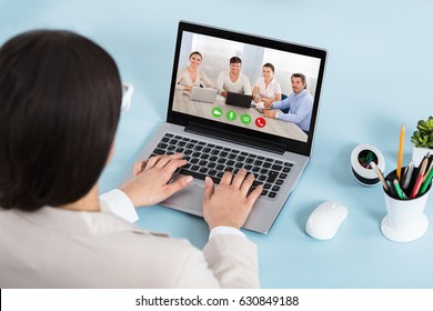 Rear View Of A Businesswoman Chatting With Her Colleague On Video Conference Using Laptop