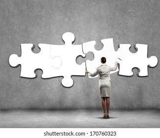 Rear view of businesswoman connecting white puzzle