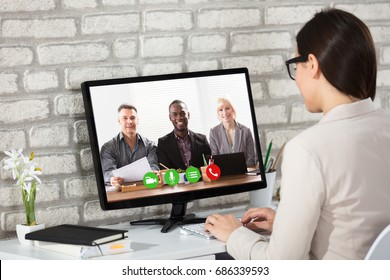 Rear View Of A Businesswoman Doing Video Conference With Her Colleagues On Computer In Office