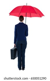 Rear view of businesswoman holding red umbrella and briefcase against white background