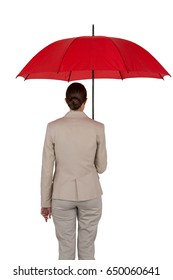 Rear view of businesswoman holding red umbrella against white background
