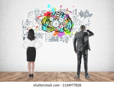 Rear view of a businesswoman with long black hair and a businessman in a gray suit scratching his head and looking at a concrete wall with a cog brain and business scheme sketches on it.