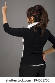 Rear view of a businesswoman pretending to working on virtual screen