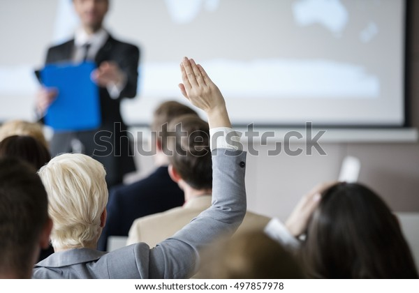 Rear view of businesswoman raising hand during seminar