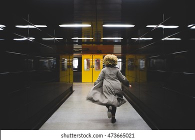 Rear view of businesswoman running to catch the subway train, which is already leaving the underground station.