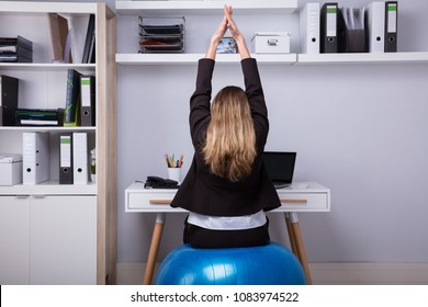 Rear View Of A Businesswoman Sitting On Fitness Ball Stretching Her Arms