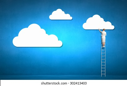 Rear view of businesswoman standing on ladder and reaching cloud