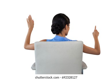 Rear view of businesswoman touching interface white sitting on chair against white background