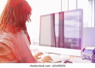 Rear view of businesswoman using desktop computer in creative office