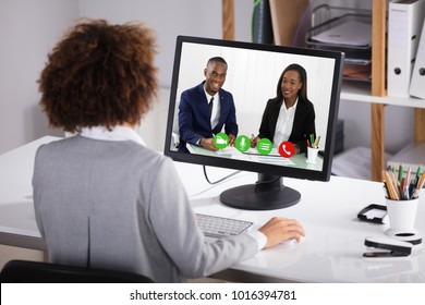Rear View Of A Businesswoman Video Conferencing Colleagues On Computer In Office
