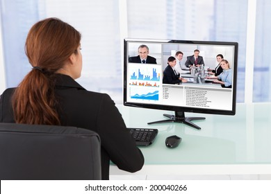 Rear view of businesswoman video conferencing with team on computer at desk in office