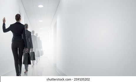 Rear view of businesswoman walking in office corridor