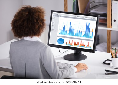 Rear View Of A Businesswoman Working On Graph On Computer In Office