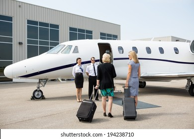 Rear view of businesswomen with luggage walking towards private jet while pilot and airhostess standing by