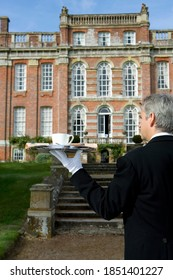 Rear view of a butler holding up a tray containing a cup of tea and a newspaper in front of a huge manor house on a bright, sunny day
