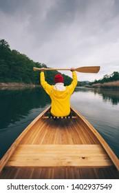 Rear view of canoeist girl in yellow raincoat holding oars high.  Woman paddling canoe in the rain