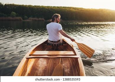 Rear view of canoeist paddling the canoe with oar. Man enjoy canoeing