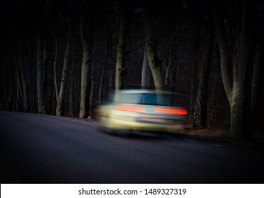 Rear view of car in blurred motion in dark forest at night