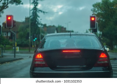 Rear view of a car, displaying stop ligths and red lights, traffic signals, at dusk, in poor visibility conditions. Concept photo, with shallow depth of field and toned colors.