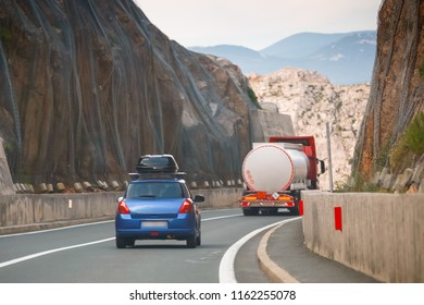 Rear view of car and tank truck driving over Krk brige in Croatia.