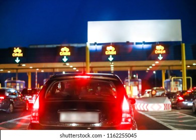 Rear view of car waiting in the line with empty white panel on the highway toll booth with cash signs at sunset.