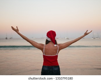 Rear view of carefree woman happy in santa hat and red swimsuit enjoying sunset on the tropical paradise beach. Vacation, travel, tourism concept