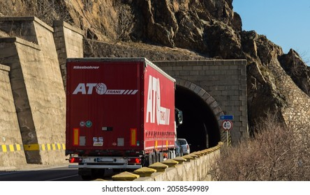 Rear view of cargo truck on the mountain road, at the entrance to the tunnel. Red truck belonging to the Slovak company ATO TRANS. Import and export of goods concept. Orsova, Romania, October 15, 2021
