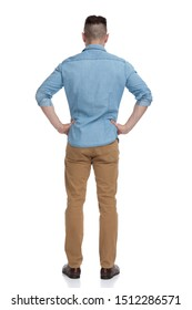 rear view of a casual man with blue shirt standing with his hands on his waist pensive on white studio background