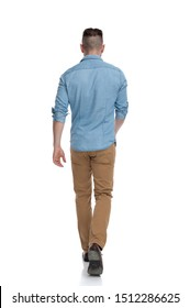 rear view of a casual man with blue shirt walking lonely on his path on white studio background