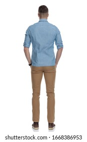 Rear view of casual man holding his hands in his pockets while wearing blue shirt, standing on white studio background