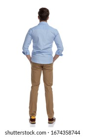 Rear view of casual man holding hands in pockets while wearing shirt and standing on white studio background