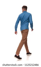 rear view of casual man walking and looking to side on white background, full length picture