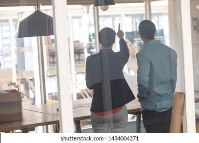 Rear view of Caucasian architects interacting with each other in a modern office