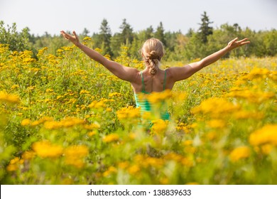 rear view of Caucasian blonde middle-aged woman practicing yoga arms stretched in the middle of a meadow of yellow ragweed flowers.  Blue Hill, Maine, Summer